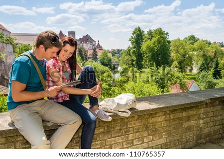 Young happy couple on vacation in city looking at map - stock photo