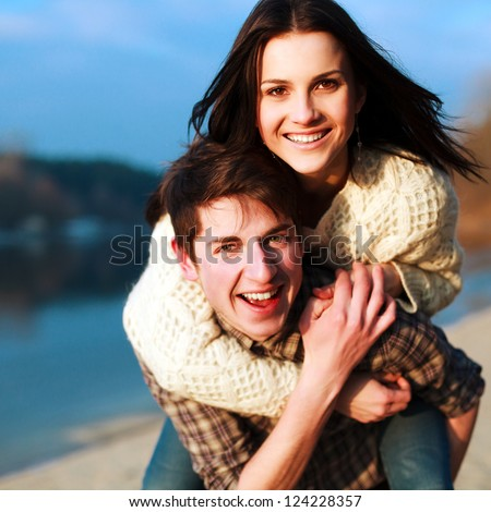 Young happy couple outdoor portrait. Beautiful boy and girl have fun on the beach. - stock photo