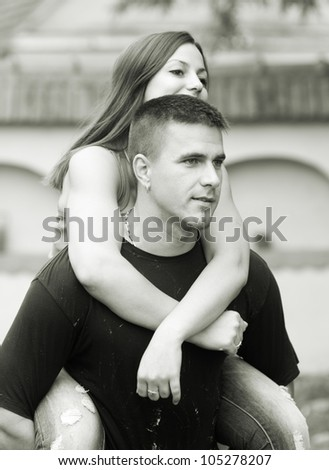 Young happy couple piggy back riding outdoor - monochrome photo. - stock photo
