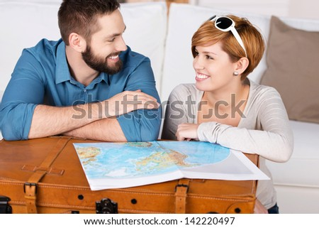 Young happy couple planning a travel with map - stock photo