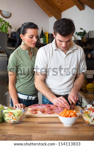 Young happy couple preparing lunch in kitchen  - stock photo