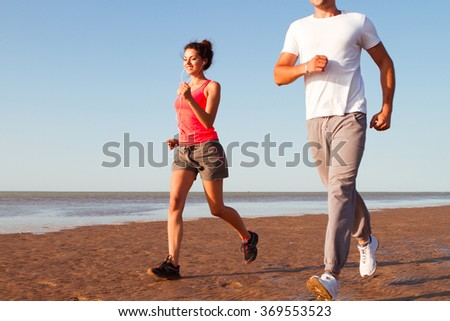 Young happy couple running beside the water at the beach. Man and woman training outdoors together. - stock photo