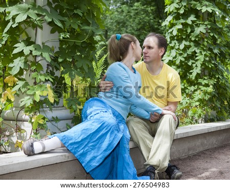 Young happy couple sits in the arbour twined greens - stock photo