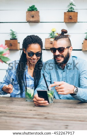 Young happy couple sitting at cafe and looking at mobile phone  - stock photo