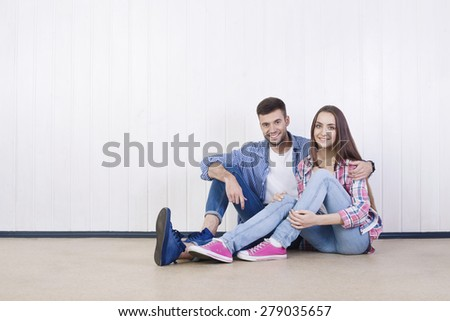 Young happy couple sitting in empty new apartment.  - stock photo