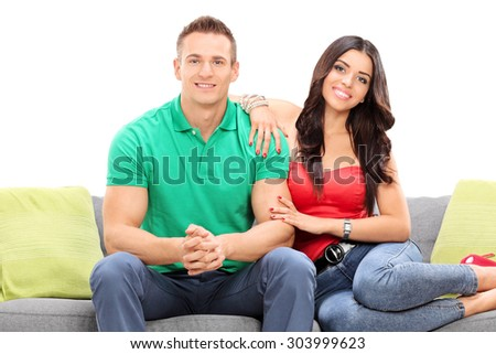 Young happy couple sitting on a sofa isolated on white background - stock photo