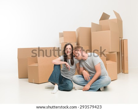 young happy couple sitting on floor in new apartment, exhausted after moving boxes - stock photo