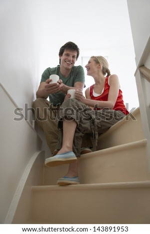 Young happy couple sitting on stairs with coffee cups - stock photo