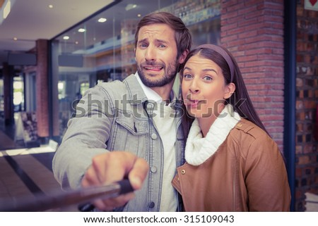 Young happy couple taking a selfie while making weird faces in front of a store - stock photo