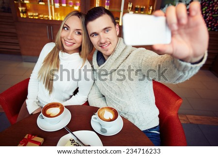 Young happy couple taking their selfie while sitting in cafe - stock photo