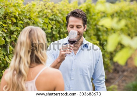 Young happy couple tasting wine in the grape fields - stock photo