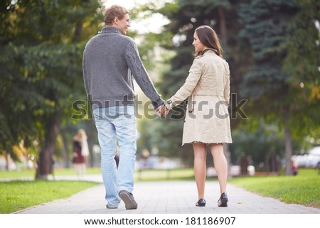 Young happy couple walking in park - stock photo