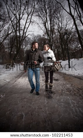 Young happy couple walking in park at evening and talking - stock photo