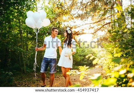 Young happy couple walking in the park. Man holing white baloons balloons. Woman hold white flowers boquet   - stock photo