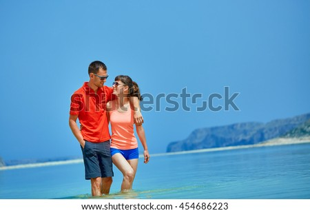 young happy couple walking on the beach at the morning. Balos beach, Crete, Greece. - stock photo