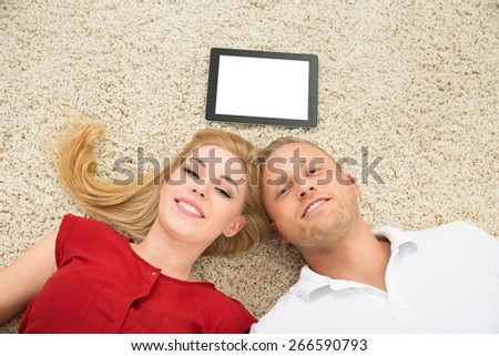 Young Happy Couple With Blank Display Digital Tablet Lying On The Carpet - stock photo
