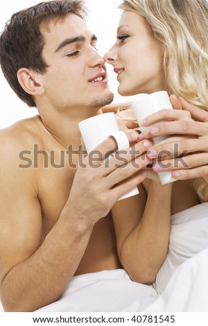 Young happy couple with coffee on the bed in bedroom - stock photo