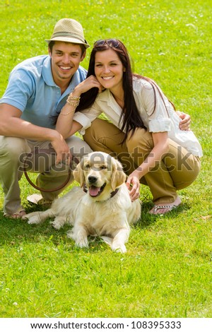 Young happy couple with Labrador dog sitting on grass - stock photo