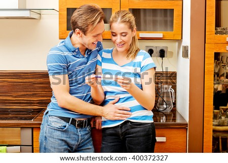 Young happy couple with pregnancy test standing in kitchen - stock photo