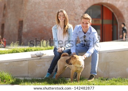 Young happy couple with their dog in the city - stock photo