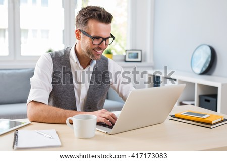Young happy designer working on laptop from home - freelance concept - stock photo