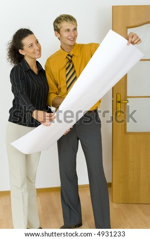 Young, happy designers couple holding plans. Standing in flat's room. Looking at something - stock photo