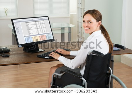 Young Happy Disabled Businesswoman On Wheelchair Using Computer In Office - stock photo
