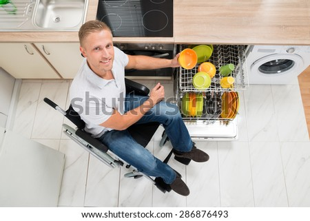 Young Happy Disabled Man On Wheelchair Arranging Plate In Dish Rack - stock photo