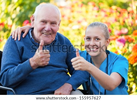 Young happy doctor showing thumbs up with his elderly patient. - stock photo