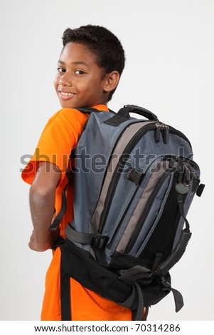 Young happy ethnic schoolboy wearing rucksack - stock photo