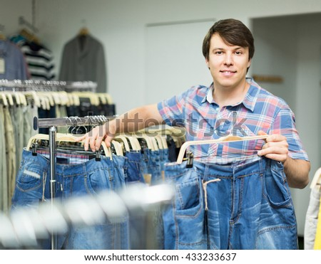 Young happy european male chooses jeans at clothing store - stock photo