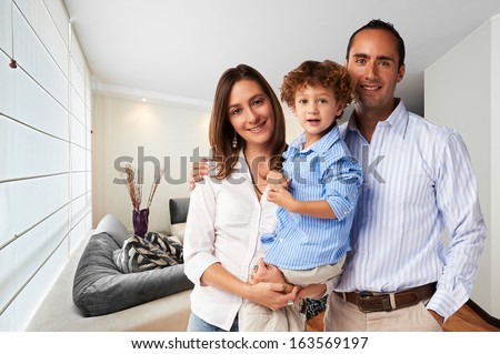 Young happy family at home: Mother, father and son - stock photo