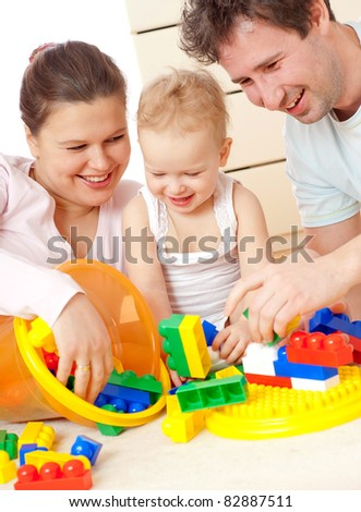 Young, happy family in a room interior - stock photo