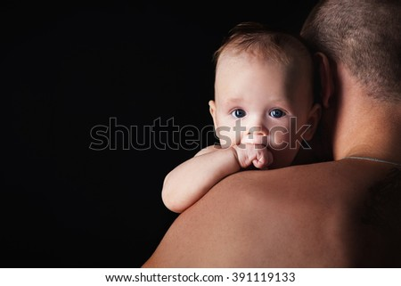 Young happy family in the studio on a dark background in dark clothes holding a baby on the hands and looks at him. - stock photo