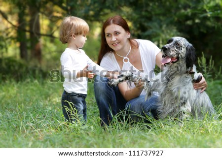 young happy family - mother and child - with dog in park - stock photo