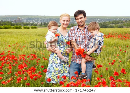 Young happy family of four having fun together outdoor. - stock photo