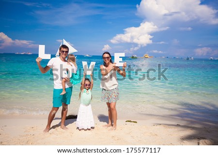 Young happy family of four on tropical vacation with word LOVE - stock photo