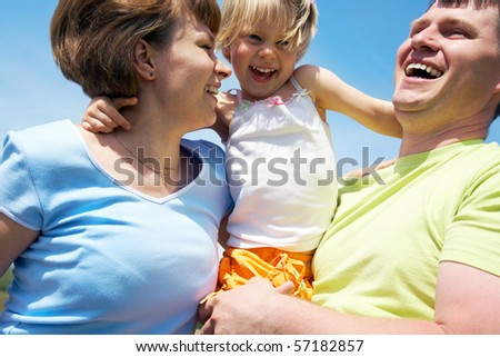 Young happy family playing with daughter outdoors background on the blue sky - stock photo