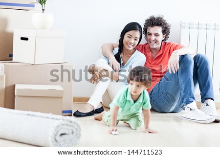 Young happy family relaxing after they have moved into their new home. - stock photo