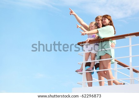 young happy family rests on yacht and indicates something interesting in sea - stock photo