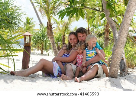 Young happy family under the palm on tropical sand beach - stock photo