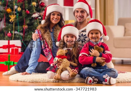 Young happy family while celebrating Christmas at home - stock photo
