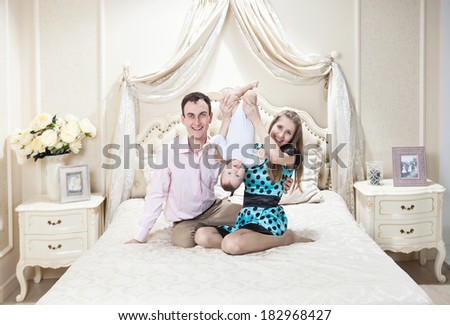Young happy family with a baby having fun on bed at home - stock photo