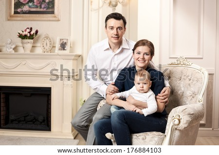 Young happy family with a baby indoors  - stock photo