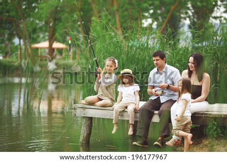 Young happy family with kids fishing in pond in summer - stock photo