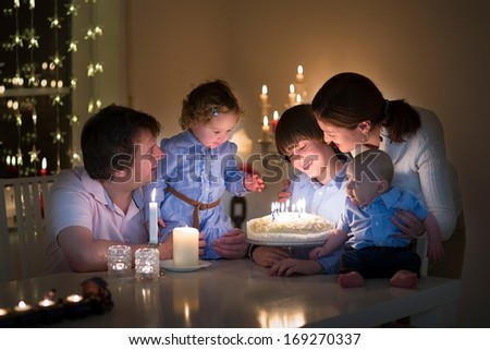 Young happy family with three kids celebration the birthday of their son blowing out the candles on a cake in a dark living room  - stock photo