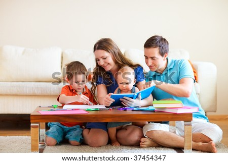 Young happy family with two kids drawing and reading together - stock photo