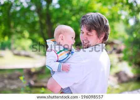 Young happy father holding his baby son, cute little smiling boy, having fun together enjoying a warm sunny day in a park during summer vacation - stock photo