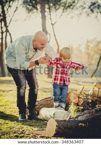 young happy father playing with excited little cute son walking and climbing on tree logs in the park having fun outdoors on a sunny Autumn day in family love and childhood concept - stock photo
