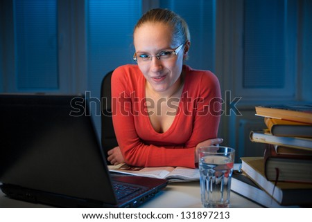 young  happy female college student smiling behind her table on a late evening,  funny night procrastination concept - stock photo